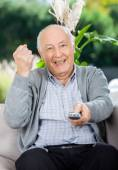 Cheerful Senior Man Clenching Fist While Using Remote Control — Stock Photo