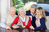 Grandchildren Looking At Grandparents Using Digital Tablet — Stock Photo