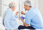 Caretaker Guiding Prescription To Senior Man — Stock Photo