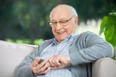 Smiling Senior Man Text Messaging Through Mobilephone — Stock Photo