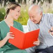Smiling Female Nurse Looking At Senior Man While Reading Book — Stock Photo #55748989