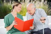 Smiling Female Nurse Looking At Senior Man While Reading Book — Stock fotografie