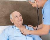 Senior Man Looking At Caretaker Examining Him With Stethoscope — Stock Photo