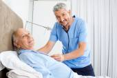 Portrait Of Smiling Caretaker Examining Senior Man — Stock Photo