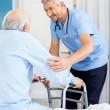 Caretaker Assisting Senior Man To Use Walking Frame — Stock Photo #55750457