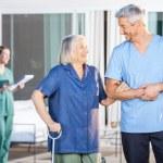 Happy Nurse Assisting Senior Woman To Walk — Stock Photo #55750861