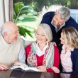 Happy Couple With Grandparents Reading Book In Nursing Home — Stock Photo #55750921