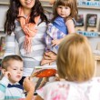 Family Looking At Librarian Showing Book — Stockfoto #55752911