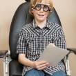 Постер, плакат: Boy With Trial Frame Holding Test Chart At Optician