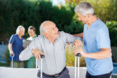 Male And Female Caretakers Helping Elderly People — Stock Photo