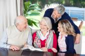 Happy Couple With Grandparents Reading Book In Nursing Home — Stock Photo