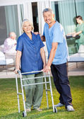 Happy Caretaker Helping Senior Woman To Use Zimmer Frame — Stock Photo