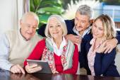 Senior Woman Using Digital Tablet With Family At Nursing Home — Stock Photo