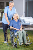 Male Nurse Standing With Senior Woman On Wheelchair — Stock Photo