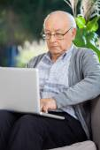 Senior Man Using Laptop At Porch — Stockfoto