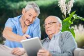 Male Nurse Showing Something To Senior Man On Digital Tablet — Stock Photo