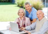 Caretaker And Senior Couple With Laptop At Nursing Home — Stock Photo