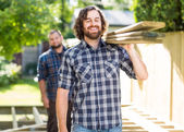 Carpenter With Coworker Carrying Planks Outdoors — Stock Photo