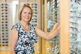 Female Customer Selecting Glasses In Optician Store — Stock Photo