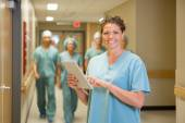 Surgeon Holding Digital Tablet In Hospital Corridor — Stock Photo