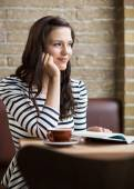 Woman With Hand On Chin Looking Away In Coffeeshop — Stock Photo
