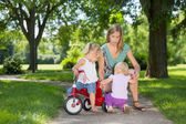 Mother And Children With Tricycle In Park — Zdjęcie stockowe