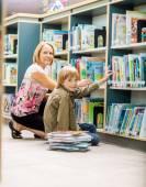 Boy And Teacher Selecting Books From Bookshelf — Stock Photo