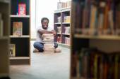 Happy Student With Stacked Books Sitting In Library — Stock Photo