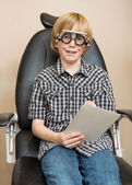 Boy With Trial Frame Holding Test Chart At Optician — Stock Photo