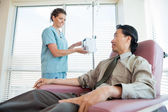 Nurse Looking At Patient While Adjusting IV Machine — Stock Photo