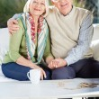 Senior Man Sitting With Arm Around Woman On Couch — Stock Photo #55939395