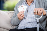 Elderly Man Showing Four Aces While Sitting — Stock Photo