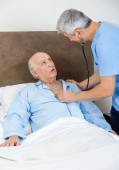 Caretaker Examining Senior Man With Stethoscope — Stock Photo