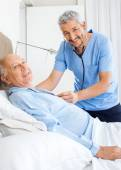 Portrait Of Happy Caretaker Examining Senior Man — Stock Photo