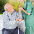 Female Caretaker Helping Elderly Man To Get Up From Couch — Stockfoto #55940161