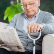 Elderly Man Reading Newspaper At Nursing Home Porch — Stok fotoğraf #55940191