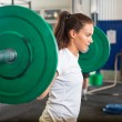 Fit Woman Lifting Barbell in Gym — Stock Photo #55940261