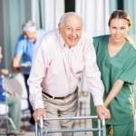 Female Caretaker Helping Senior Man In Using Zimmer Frame — Stock Photo #55940705