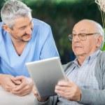 Male Caretaker Looking At Senior Man Using Tablet Computer — Stock Photo #55940811