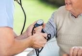Male Doctor Checking Blood Pressure Of Senior Man — Stock Photo