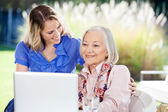 Happy Granddaughter With Senior Woman Using Laptop On Porch — Foto Stock