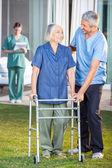 Caretaker Helping Senior Woman To Use Walking Frame — Stock Photo