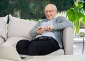 Happy Senior Man Text Messaging Through Smartphone At Porch — Stock Photo