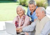 Caretaker Watching Senior Couple Using Laptop — Stock Photo