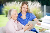 Happy Grandmother And Granddaughter Using Digital Tablet — Foto Stock