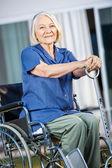 Smiling Senior Woman Sitting On Wheelchair At Yard — Stock Photo