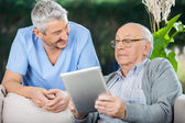 Male Caretaker Looking At Senior Man Using Tablet Computer — Stock Photo