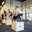 Постер, плакат: Athletes Doing Box Jumps At Gym