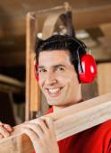 Happy Carpenter Carrying Wooden Plank On Shoulder — Stockfoto