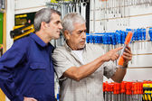Customer Examining Packed Screwdriver While Vendor Looking At — Stockfoto